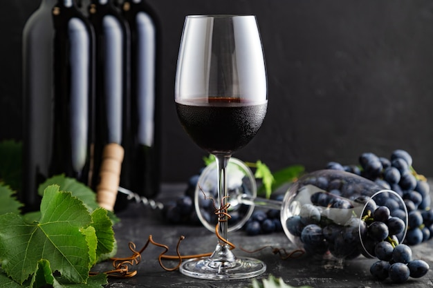 Kieliszek do wina z zimnym czerwonym winem. butelek wina, kiści winogron z liśćmi i winorośli na ciemnym tle rustykalnym betonu. skład wina na czarnym kamiennym stole.