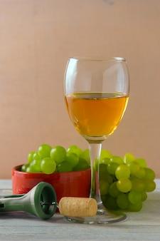 Kieliszek do wina, zielone winogrona na talerzu na stole.