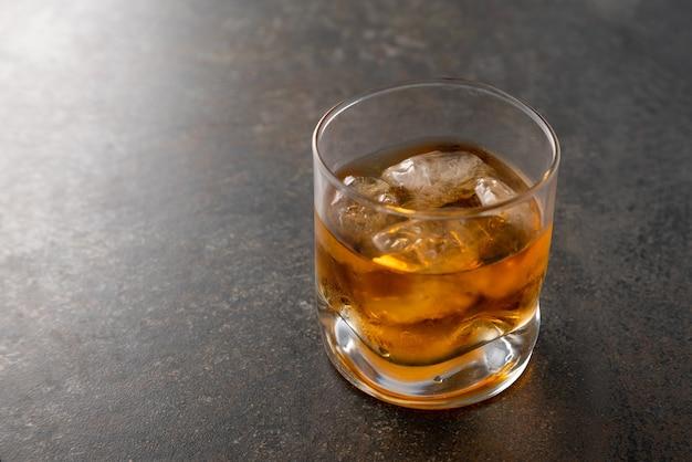 Kieliszek dojrzałej złotej whisky z kostkami lodu na stole.