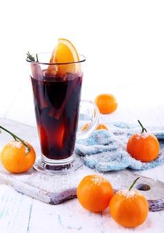 Kieliszek gorącego grzanego wina z kawałkiem pomarańczy i mandarynek na desce do krojenia i kolorowym drewnianym stole na białym tle