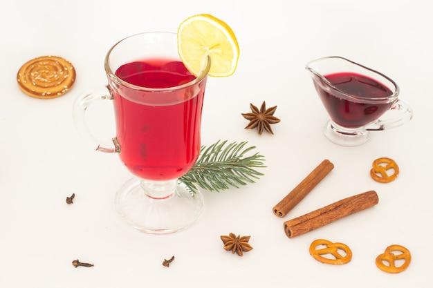 Kieliszek grzanego wina i plasterka cytryny, anyżu gwiazdkowatego na białym tle
