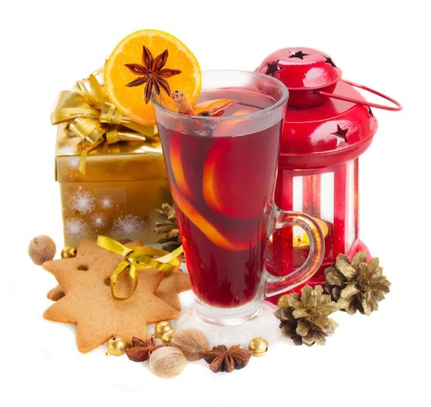 Kieliszek grzanego wina świątecznego z pudełkiem prezentowym i latarnią na białym tle