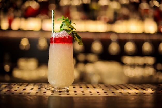 Kieliszek jasnego słodkiego tropikalnego soczystego koktajlu ananasowego z czerwonym likierem ozdobionym listkami mięty