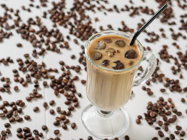 Kieliszek kawy mrożonej i rurka koktajl na tle rozrzuconych ziaren kawy na białym stole. orzeźwiający i orzeźwiający napój z ziaren kawy i mleka.