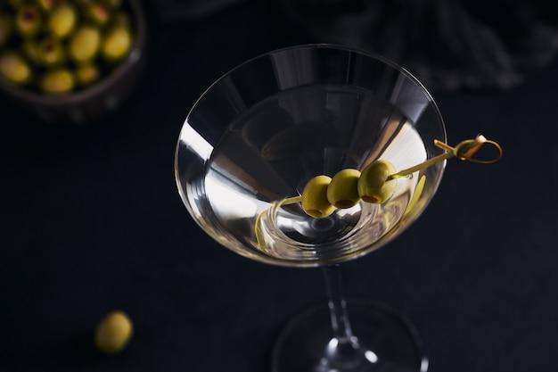Kieliszek klasycznego wytrawnego koktajlu martini z oliwkami na stole z ciemnego kamienia na tle czerni.