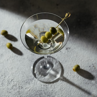 Kieliszek klasycznego wytrawnego koktajlu martini z oliwkami na szarym kamiennym tle