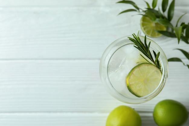 Kieliszek koktajl z limonką na białym drewnianym stole