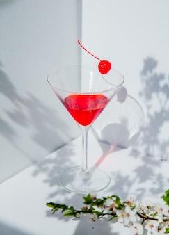 Kieliszek koktajlowy i czerwona wiśnia w pobliżu gałęzi drzewa wiśni kwiat w białym rogu. naturalne światło