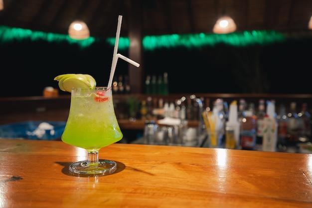 Kieliszek koktajlowy midori na drewnianym blacie barowym w nocy, zielony napój alkoholowy, sok owocowy zmieszany z alkoholem, koncepcja imprezy