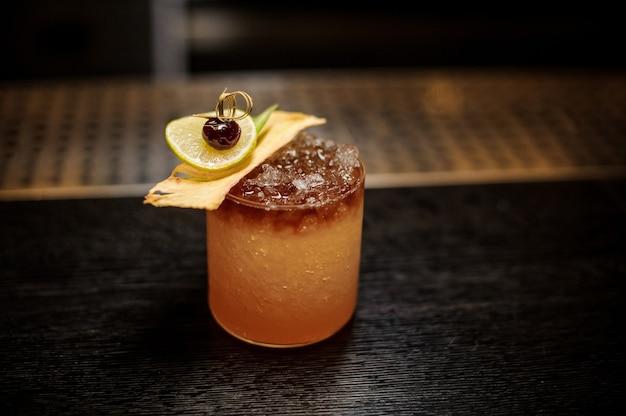 Kieliszek koktajlowy wypełniony smacznym słodkim napojem alkoholowym z lodem i kawałkami owoców na blacie barowym