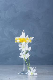 Kieliszek koktajlowy ze świecą i białymi kwiatami na szarym tle