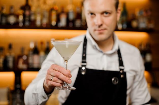Kieliszek koktajlowy ze świeżym napojem alkoholowym w dłoni barmanów