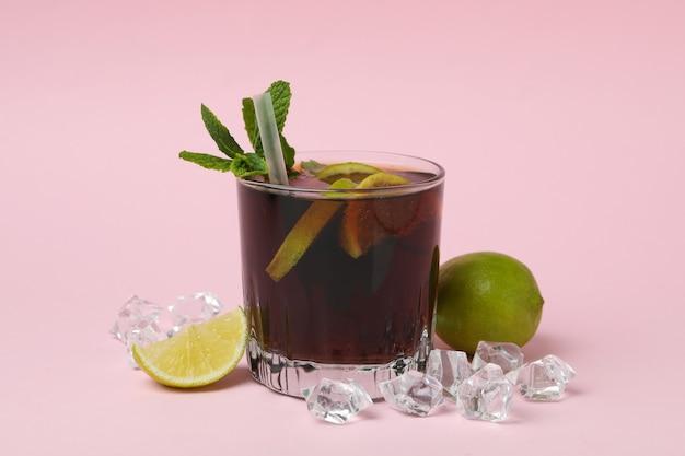 Kieliszek koktajlu cuba libre na różowej powierzchni