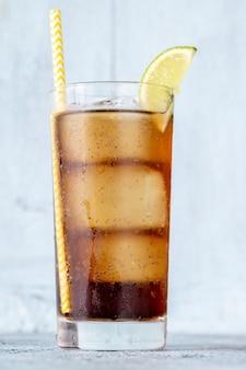Kieliszek koktajlu cuba libre z kawałkiem limonki