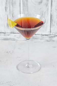 Kieliszek koktajlu martinez przyozdobiony skórką z cytryny