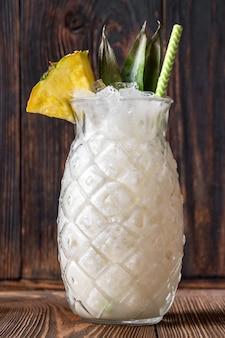 Kieliszek koktajlu pina colada przyozdobiony kawałkiem ananasa