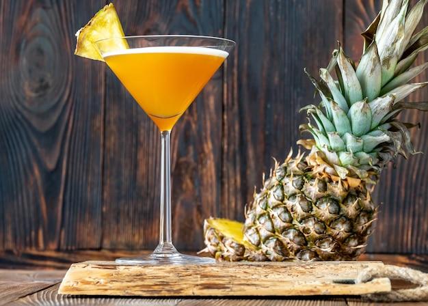 Kieliszek koktajlu rajdowca downhill przyozdobiony kawałkiem ananasa
