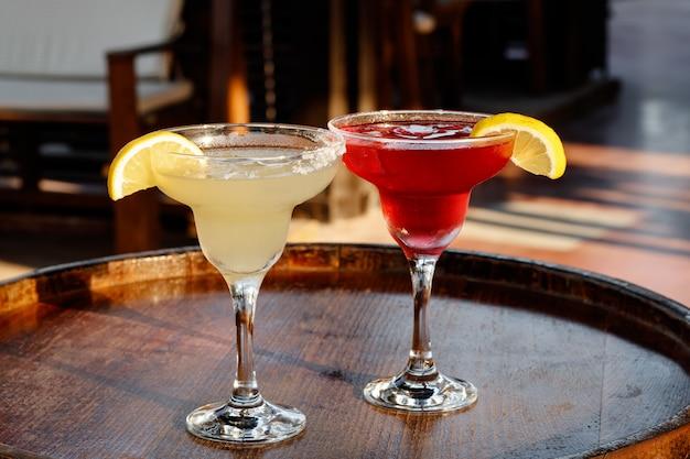 Kieliszek koktajlu w barze. w pubie dwa słodkie koktajle cosmopolitan i margarita. mieszane napoje alkoholowe. koncepcja party na plaży, wakacje.
