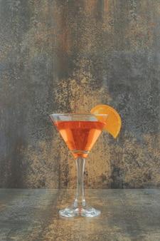 Kieliszek koktajlu z plasterkiem pomarańczy na marmurowym stole.