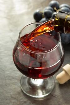 Kieliszek koniakowy i winogrona na stole
