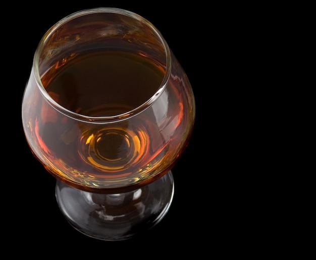 Kieliszek koniakowy z brandy na czarnym tle