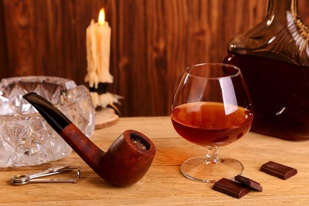 Kieliszek koniaku, czekolady i fajka na dębowym stole
