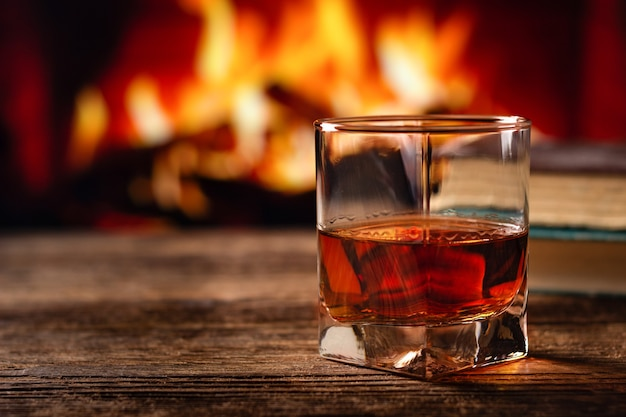Kieliszek koniaku lub whisky. rozmycie tła płonącego kominka.