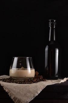 Kieliszek kremowego likieru i lodu, obok czarna butelka