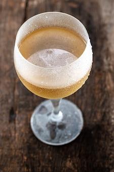 Kieliszek kryształowy do białego wina podawany na bardzo zimno, na rustykalnym stole na czarnym tle.