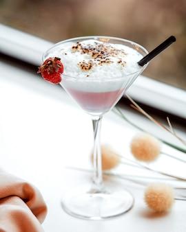 Kieliszek martini z piankowym koktajlem truskawkowym przyozdobionym truskawką