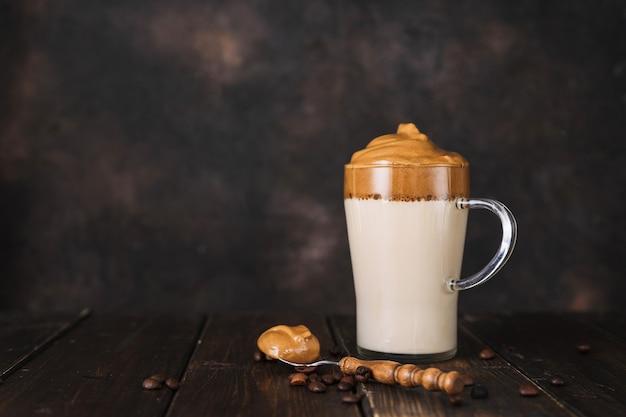 Kieliszek modnej kawy dalgona i łyżeczka