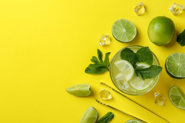 Kieliszek mojito koktajl i składniki na żółtym tle