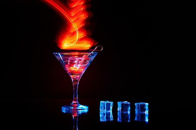 Kieliszek neonowego martini strzał z długim czasem naświetlania. czerwone światła klubowe.
