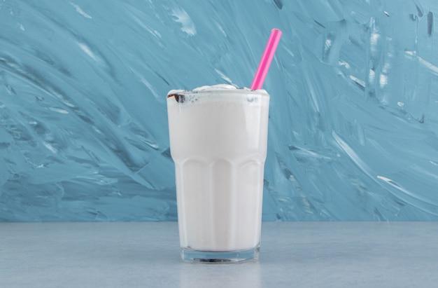 Kieliszek pysznego mleka morszczuka na marmurowym tle. wysokiej jakości zdjęcie