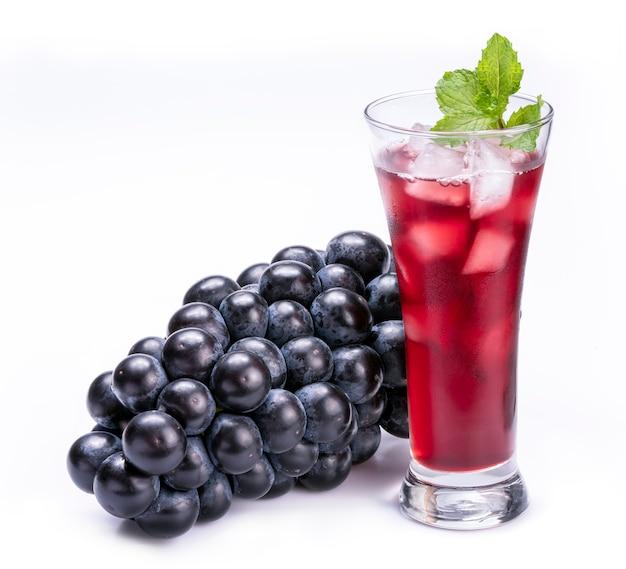 Kieliszek soku z czerwonych winogron i owoców winogron na białym tle na białej przestrzeni.