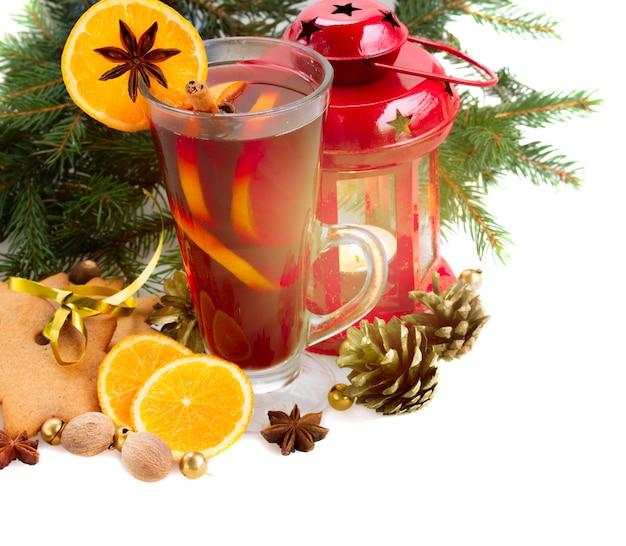 Kieliszek świątecznego grzanego wina z jodłą i płonącą latarnią na białym tle