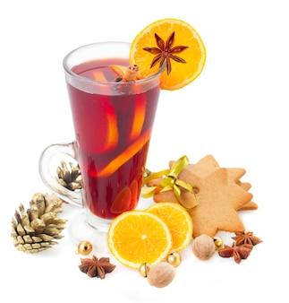 Kieliszek świątecznego grzanego wina z pomarańczami na białym tle