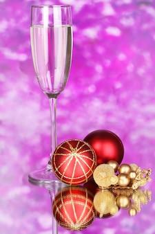 Kieliszek szampana i bombki na fioletowym tle