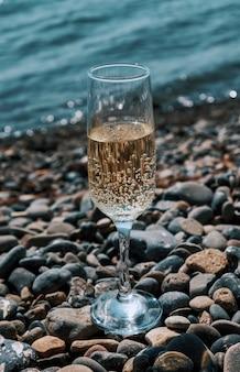 Kieliszek szampana na błękitnej plaży w słoneczny dzień.