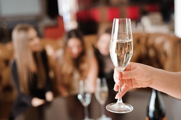 Kieliszek szampana na tle przyjaciół na imprezie