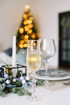 Kieliszek szampana na zdobionym stole w boże narodzenie