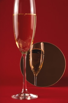 Kieliszek szampana z odbiciem w małym okrągłym lusterku na czerwono