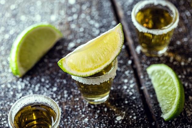 Kieliszek tequili, napoju kultury meksykańskiej, zrobiony z destylowanego alkoholu, cytryny, soli i niebieskiej agawy