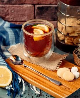 Kieliszek tequilli podany z plastrami soli i cytryny