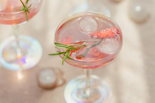 Kieliszek truskawkowego koktajlu lub mocktaila, orzeźwiający letni napój z kruszonym lodem i gazowaną wodą na świetle