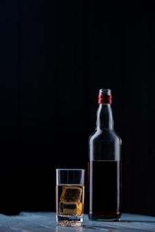 Kieliszek whisky i butelka na drewnianym stole