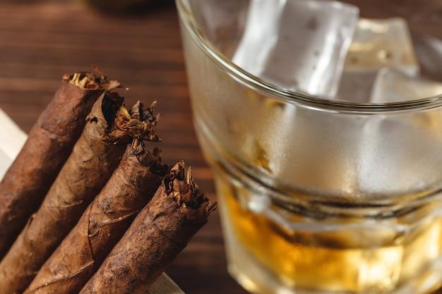 Kieliszek whisky i cygara walcowane na drewnianym stole