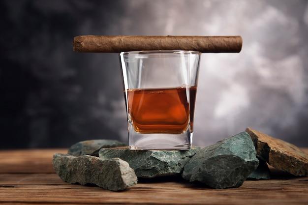 Kieliszek whisky i cygaro na kamieniu