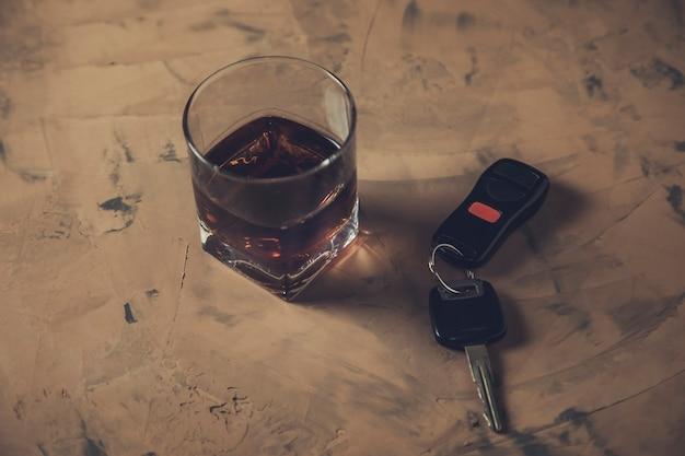 Kieliszek whisky i kluczyk do samochodu na stole