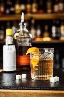 Kieliszek whisky (koniak lub brandy) z cytryną i kostkami lodu stojącymi na blacie barowym z butelką w tle